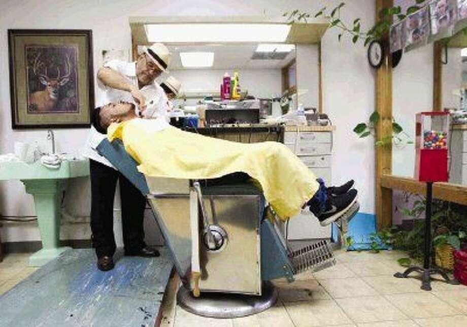 Salvador Ramos shaves a customer's beard at Dan's Barber Shop in downtown Conroe. Photo: Jason Fochtman