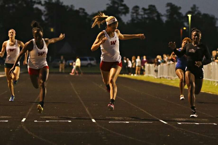 The Woodlands' Kaitlynn Lindsey beats teammate Charity Thomas to the finish line in the 200-meter dash during the District 14-5A championships on Wednesday at The Woodlands High School. Photo: Michael Minasi