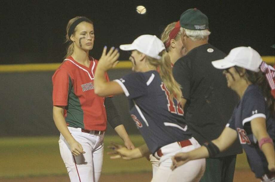 The Woodlands pitcher Abby Langkamp, left, walks back to the dugout as Atascocita celebrates after Shelby McGlaun's walk-off home run in the bottom of the 8th inning during Game 1 of a regional quarterfinal series at Porter High School Friday. To view or purchase this photo and others like it, visit HCNpics.com. Photo: Jason Fochtman