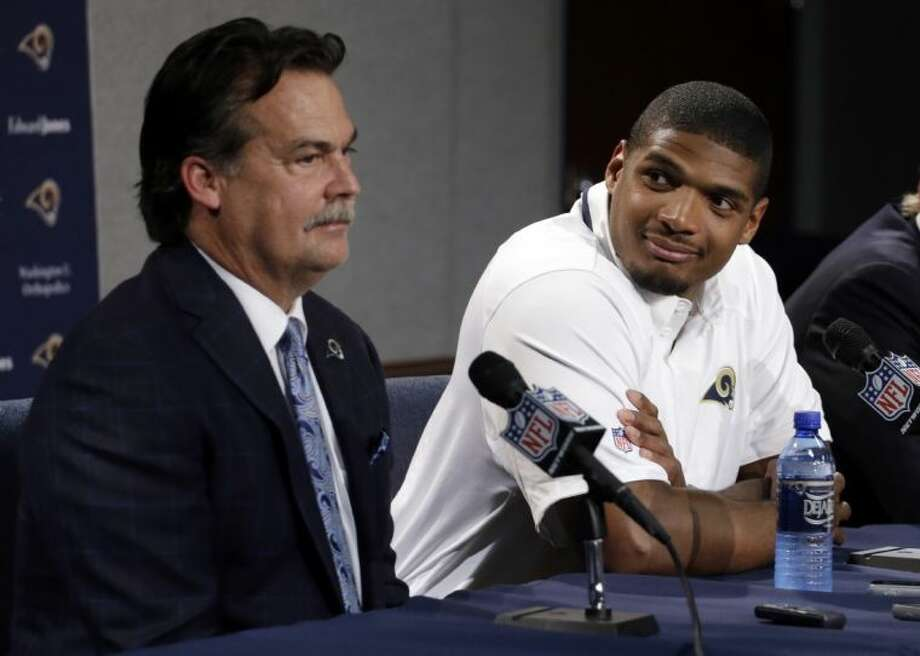 St. Louis Rams draft pick Michael Sam listens as coach Jeff Fisher speaks during a news conference on Tuesday in St. Louis. Photo: Jeff Roberson