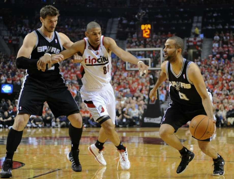 Spurs guard Tony Parker, right, missed the second half of the team's clinching game against the Portland Trail Blazers with a hamstring injury. Photo: Greg Wahl-Stephens