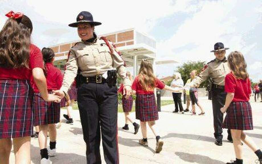 Honor Guard members Stephanie Spiller and Danny Dickson get high-fives from Sacred Heart Catholic School students before a ceremony in honor of fallen police officers at Heritage Place Park in downtown Conroe Thursday. Go to HCNpics.com to view more photos from the ceremony.