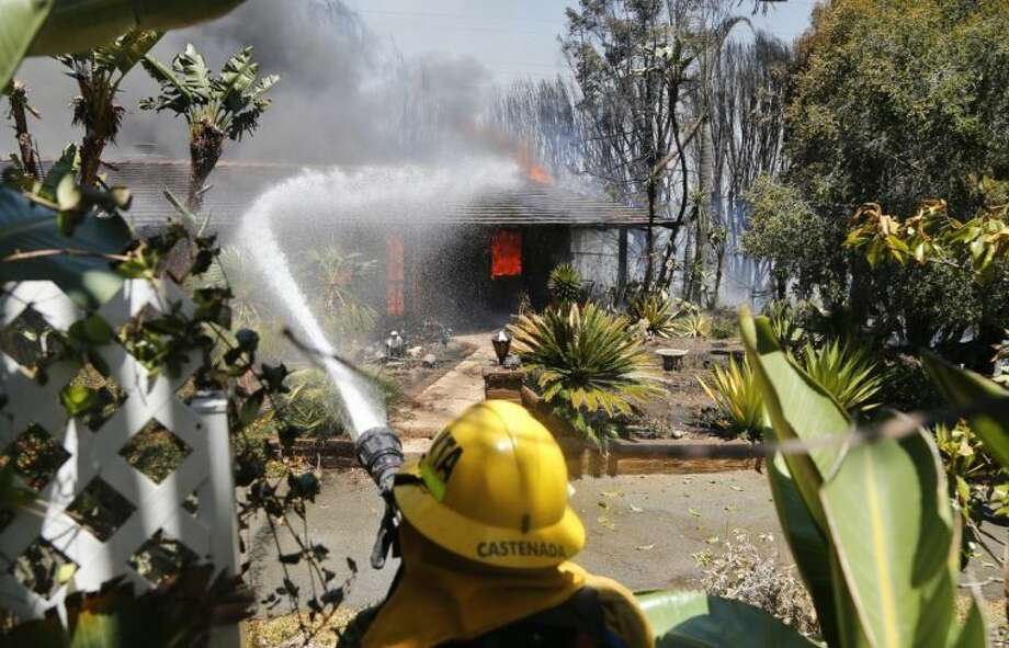 A firefighter pours water onto a fully engulfed home Wednesday , May 14, 2014, in Carlsbad, Calif. A brush fire Wednesday forced evacuation of thousands of people in the city of Carlsbad where at least two homes burned amid a Southern California heat wave that sparked several blazes. Photo: Uncredited