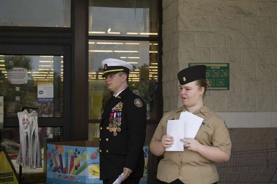Joshua Polk, Caney Creek High School graduating senior, and Megan Griffin, CCHS sophomore, help pass out informational fliers about items Kroger patrons are able to donate for military care packages Saturday.