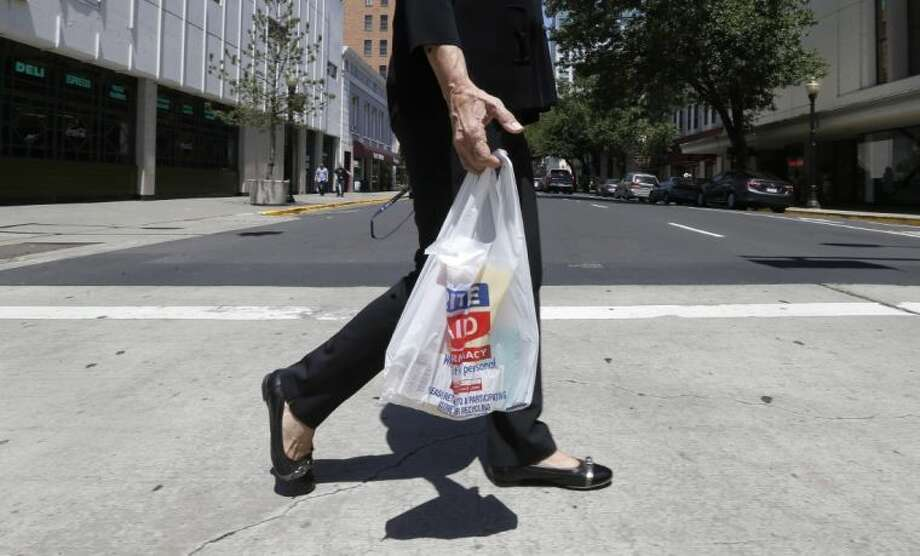A woman walks with a plastic bag in Sacramento, Calif., on Wednesday, May 14, 2014. A bill to make California the first in the nation to impose a statewide ban on plastic bags at certain retailers passed a key legislative committee on Wednesday, but the legislation faces staunch opposition from bag manufacturers working to stem a flood of local bans meant to end clutter in landfills and beaches. Photo: STF