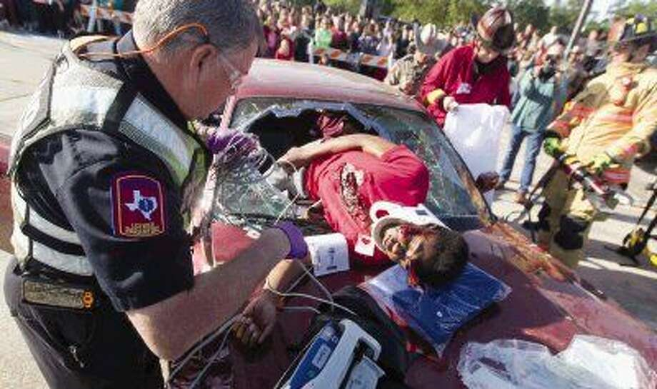 An EMS worker with Montgomery County Hospital District treats a student during Shattered Lives at Oak Ridge High School Thursday. The event featured multiple staged car accidents where emergency personnel would respond and treat victims to shows students the results of drunk driving. Photo: Jason Fochtman