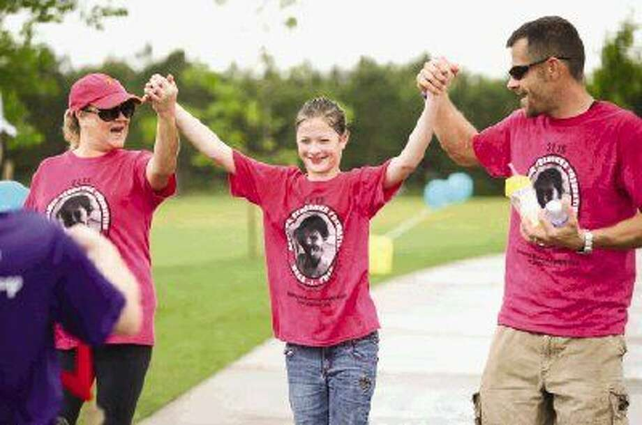Twelve-year-old Kyla Aune, center, cheers while holding hands with Jennifer and Kevin Aune, of Spring, during the Angelman Syndrome Foundation Walk Sunday at Rob Fleming Park in The Woodlands. Photo: Michael Minasi