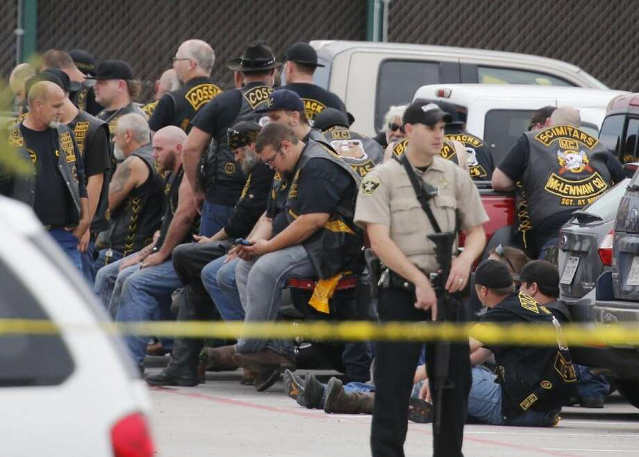"A McLennan County deputy stands guard near a group of bikers in the parking lot of a Twin Peaks restaurant Sunday in Waco, Texas. Waco Police Sgt. W. Patrick Swanton told KWTX-TV there were ""multiple victims"" after gunfire erupted between rival biker gangs at the restaurant. Photo: Rod Aydelotte"
