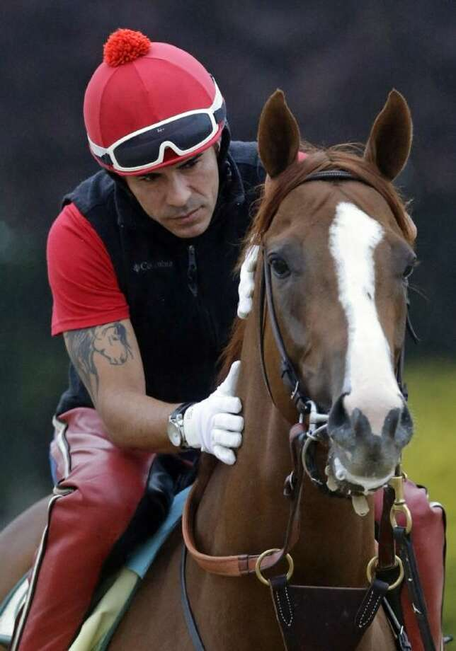 Exercise rider Willie Delgado rubs Kentucky Derby winner California Chrome's neck before a workout on Wednesday at Pimlico Race Course in Baltimore. Photo: STF