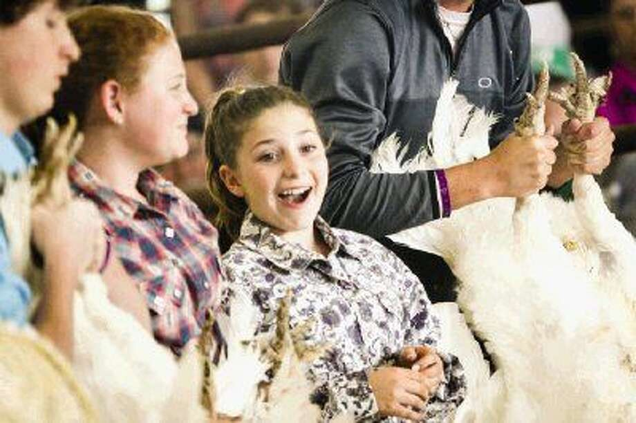 Tatum Mabry, 11, a student at New Waverly Junior High School, reacts as she wins Grand Champion for the turkey category on Saturday at the Montgomery County Fairgrounds. Tatum's sister, Rileigh Mabry, 14, also won Reserve Grand Champion in the turkey category. Photo: Michael Minasi