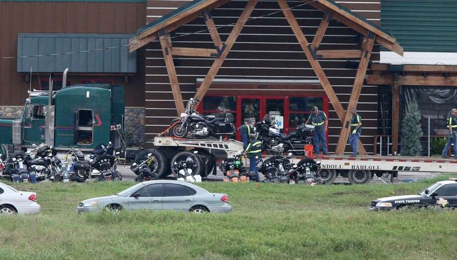 People load motorcycles on to a trailer in front of the Twin Peaks restaurant Monday in Waco. About 170 members of rival motorcycle gangs were charged with engaging in organized crime Monday, a day after a shootout at the restaurant killed nine people and wounded 18. Photo: Jerry Larson