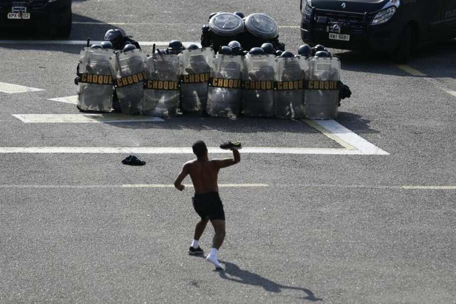 A person posing as a protester throws his shoe at police during a drill to prepare security forces for demonstrations during the upcoming World Cup in Rio de Janeiro, Brazil, Thursday, May 15, 2014. The FBI is helping to train Brazil's civilian police, military officers, municipal guards and firefighters on how to manage demonstrations ahead of the international soccer tournament that starts in June. Photo: Hassan Ammar