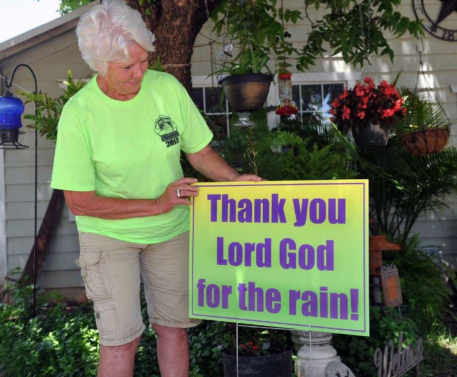 "Lynda Myracle, of Archer City, stands with one of the signs she's had printed in answer to the popular ""Pray For Rain"" yard signs seen all around the North Texas area during the 4-year drought. Myracle believes we should be thankful when prayers are answered. Photo: Torin Halsey"