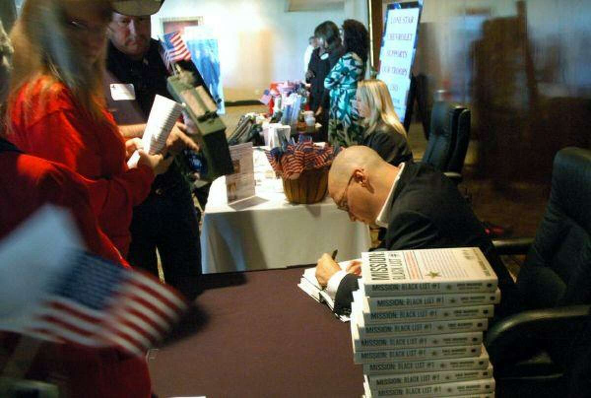 Eric Maddox signs copies of his book,