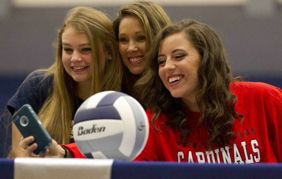 Volleyball players Savannah Rutledge, left, and Alicia Bauersfeld take a selfie with coach Candice Collins during a college signing cermeony at College Park High School Wednesday. Rutledge signed to play volleyball for Texas A&M Commerce, while Bauersfeld will play for Trinity Valley Community College. Photo: Jason Fochtman