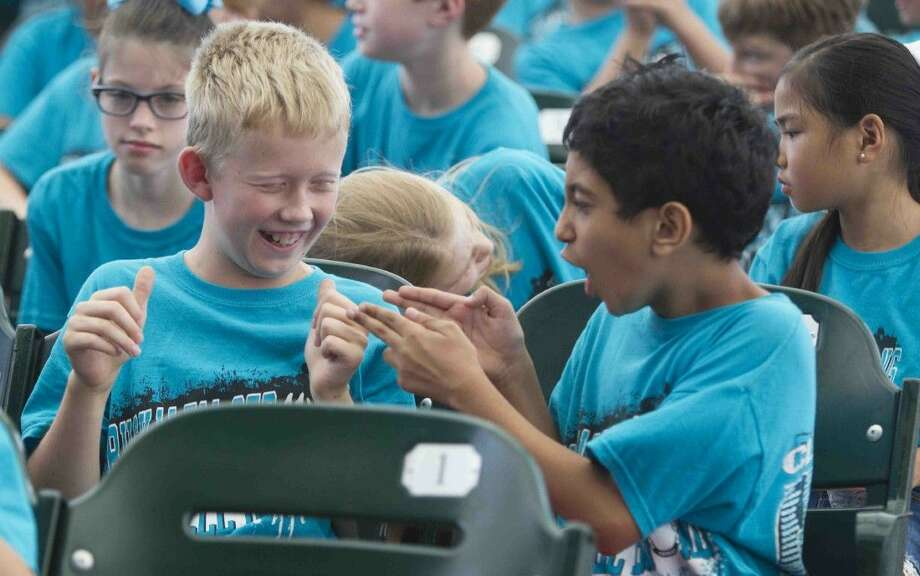 Buckalew Elementary fourth graders Joseph Moline and Abhishek Tripathi joke around before the start of the Fine Arts Education Day at Cynthia Mitchell Woods Pavilion Wednesday. Thousands of Conroe ISD students packed the music venue to hear a free performance by the Houston Symphony. Photo: Jason Fochtman