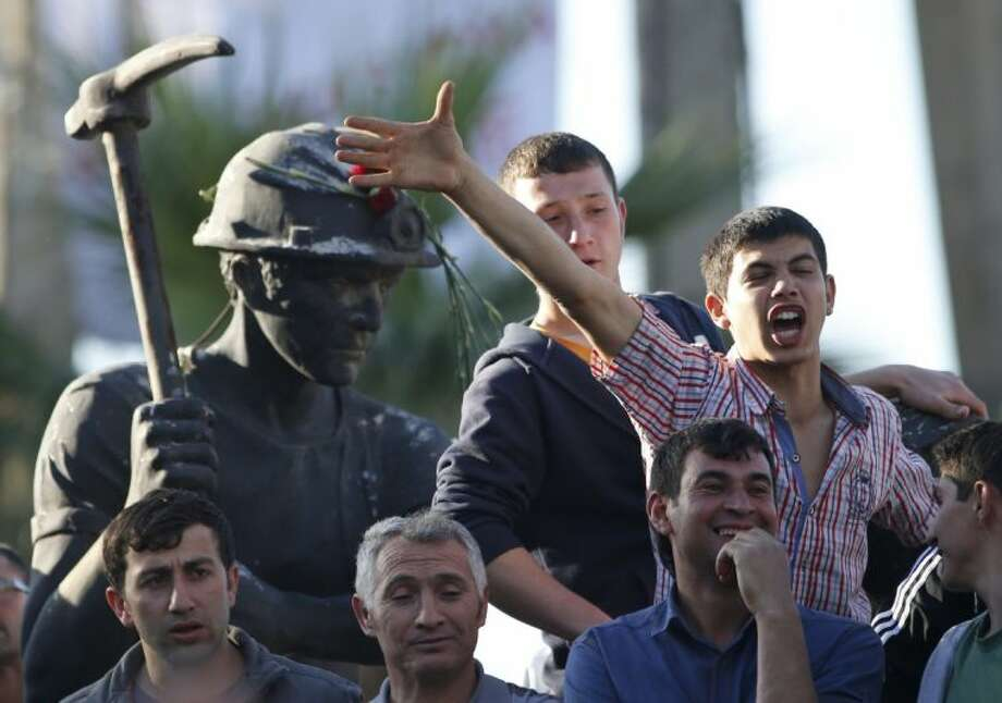 Anti-government protesters chant slogans on a monument for the town's miners, during a march in Soma, Turkey where the mine accident took place Friday..