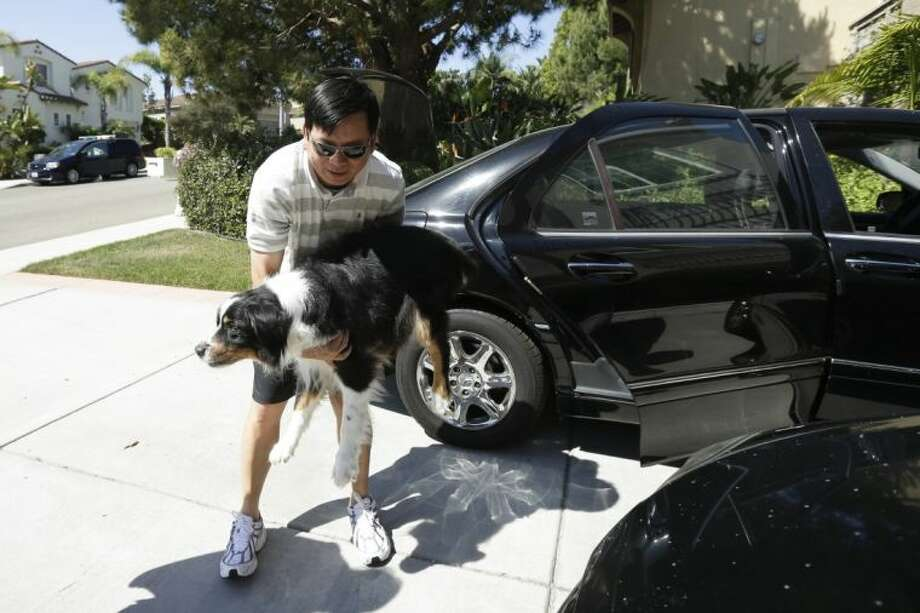 Midi Teng carries the family dog, Pup, out of the car as he arrives home from wildfire evacuations Friday in Carlsbad, Calif.