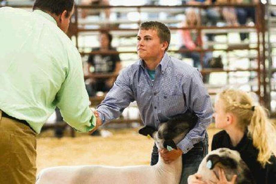 Jacob Hayden, of Splendora FFA, shakes hands with judge Bronc Fleming after being named Grand Champion in the Market Lamb division on Sunday.