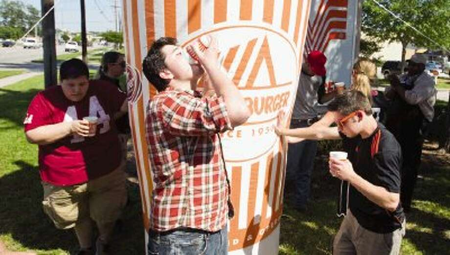 Andre Johnson drinks a milkshake during the Whataburger Challenger in Conroe Thursday. Johnson was the winner of the challenge and won Whataburger hamburgers for a year and Conroe High School received a check for $1,000 to go toward the school's Operation Graduation project. Photo: Jason Fochtman / Conroe Courier / HCN