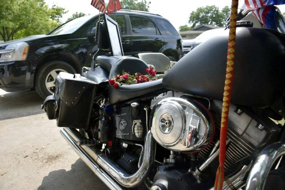 In this photo taken Wednesday roses rest on the seat of Jesus Delgado Rodriguez's motorcycle in front of his home in New Braunfels. Photo: Mark Wilson