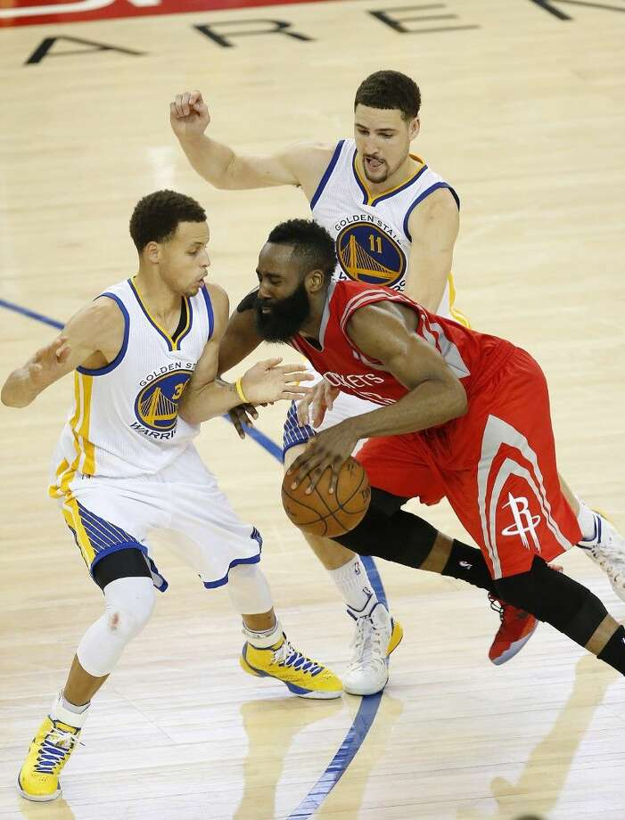 Houston Rockets guard James Harden, center, loses the ball on the game's final play as he is guarded by Golden State Warriors guard Stephen Curry, left, and guard Klay Thompson in Game 2. Photo: Tony Avelar