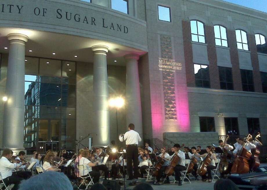 The Fort Bend Symphony performs at last year's MD Anderson Pink Lighting event. The symphony returns to this year's event, set for 7 p.m. Sept. 29 at Sugar Land Town Square.