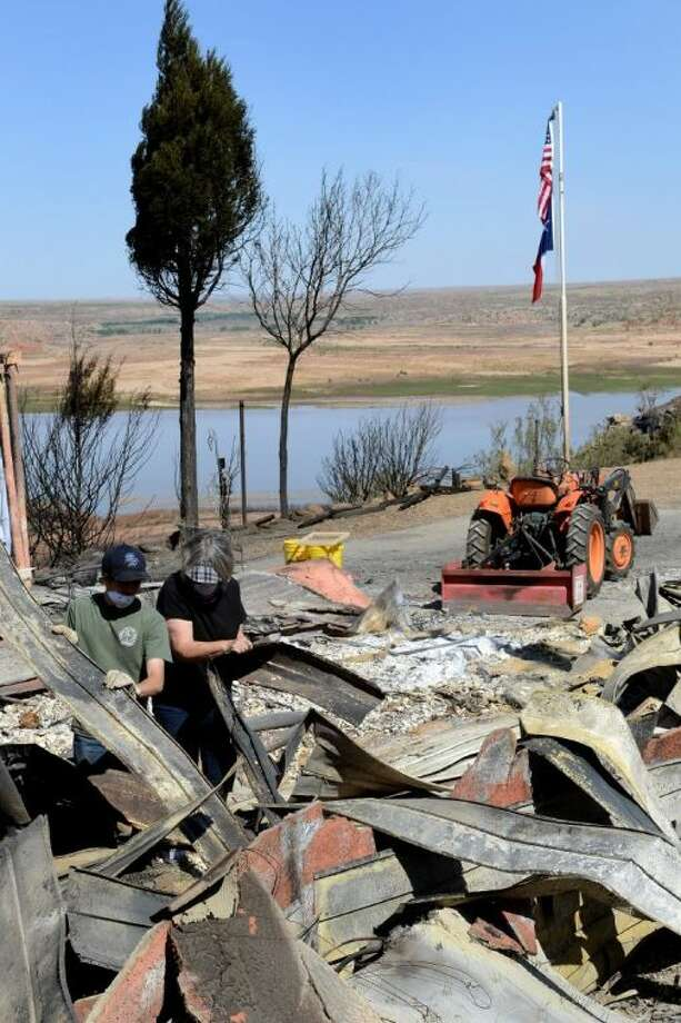 Shirley Harvey andn her grandson Jacob Harvey dig through the burnt, twisted metal that use to be their home Thursday in the Lake Meredith Harbor neighborhood in Fritch.