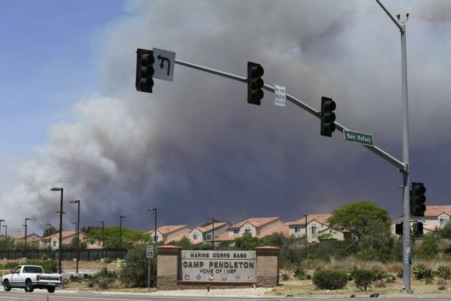 Smoke plumes rise behind the Marine Corps Camp Pendleton entrance Friday in Oceanside, Calif.