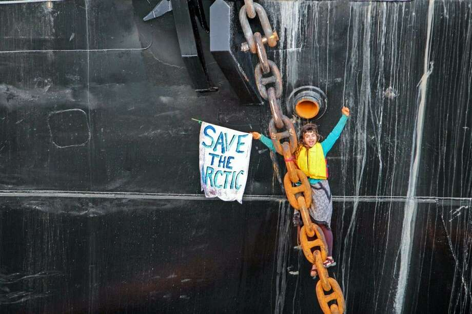 A woman identified as Chiara Rose has suspended herself in a climbing harness from the anchor chain of the Royal Dutch Shell support ship Arctic Challenger in the harbor at Bellingham, Wash. Photo: Reese Semanko