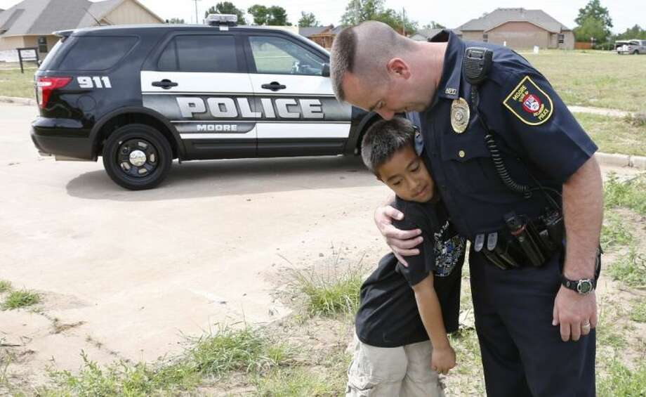 Moore police officer Travis Muehlenweg, right, hugs 10-year-old Kai Heuangpraseuth, after they met outside the new Plaza Towers Elementary school in Moore, Okla., Tuesday, May 13, 2014. Muehlenweg was photographed while helping to pull Heuangpraseuth from the rubble of Plaza Towers Elementary school following the May 20, 2013 tornado. Heuagpraseuth's mother, Jacalyn Russell, said that her son has wanted to meet Muehlenweg for nearly a year. Photo: Sue Ogrocki