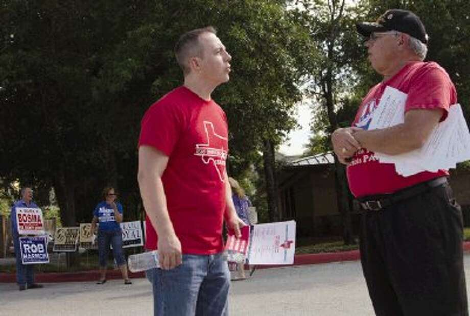Bryan Christ, of the Texas Conservative Tea Party Coalition, and Bill O'Sullivan, of the Texas Patriots PAC, argue about the motives of each group during the first day of early voting for the primary runoff elections at the South Regional Library in The Woodlands Monday. Early voting will continue until May 23. / The Conroe Courier