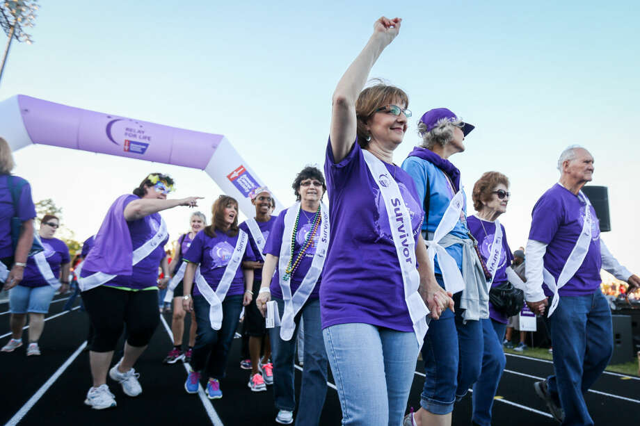 Cancer survivor Beth Benjamin, with the Faith Bible Church team, walks in The Woodlands Relay For Life on Friday at College Park High School. Photo: Michael Minasi