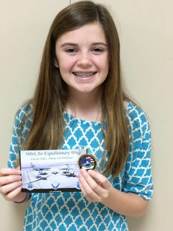 Brabham Middle School student Lily Utecht poses with a letter and Courage Coin she received from a U.S. soldier.