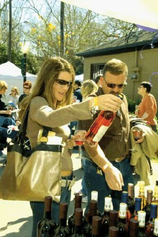 Wine enthusiasts examine the vintage of a bottle during a previous Autumn Art & Texas Wine Festival in historic Old Town Spring.
