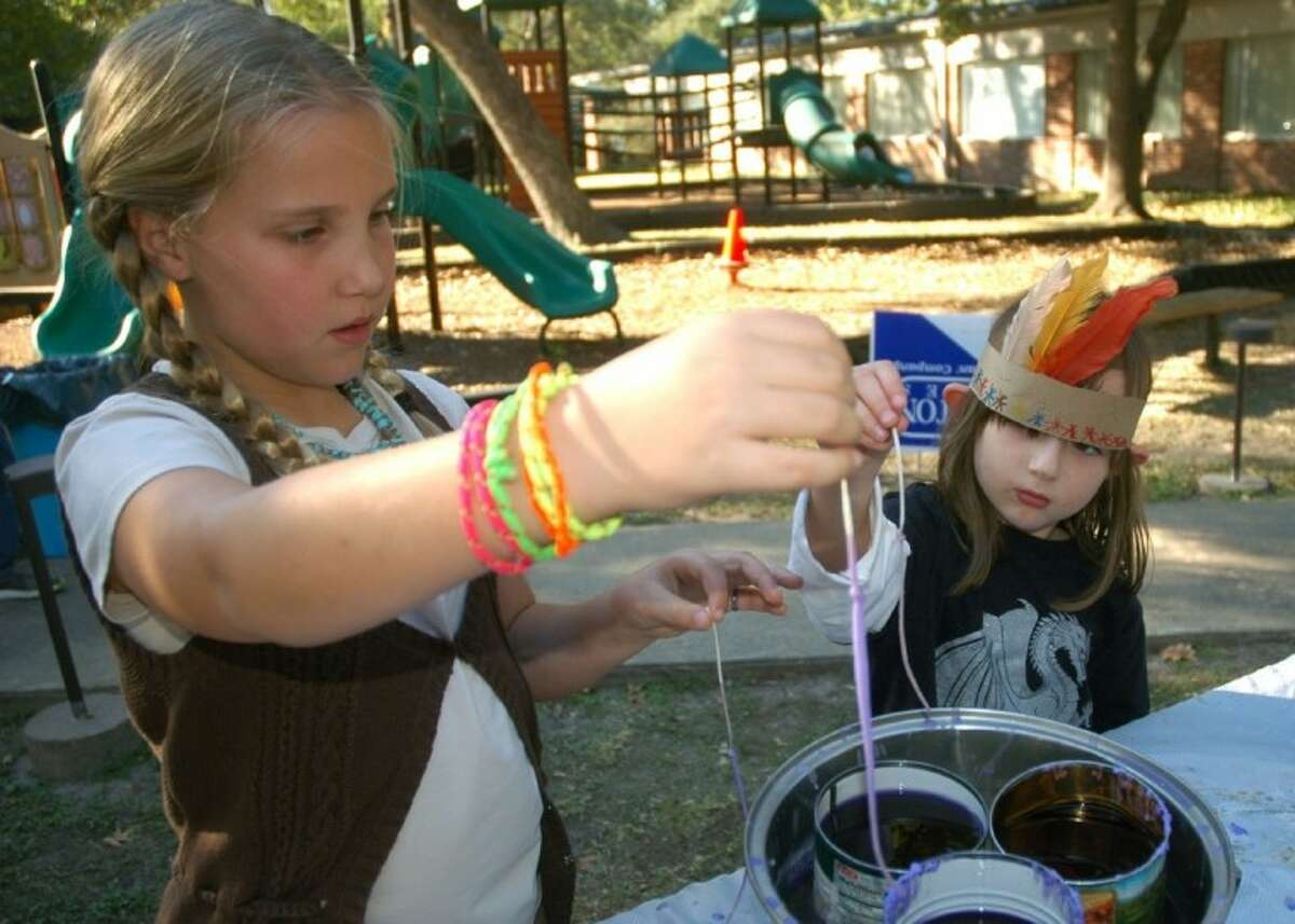 Maley Gleason (left) and Bella Warren dip wicks in hot wax to make candles Saturday at the Pilgrim Festival.