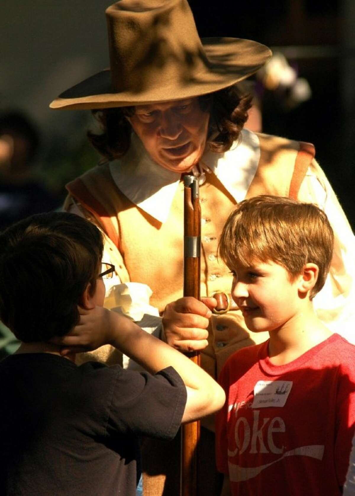 Historical recreator John Keahey, in 17th century costume, with some young visitors.
