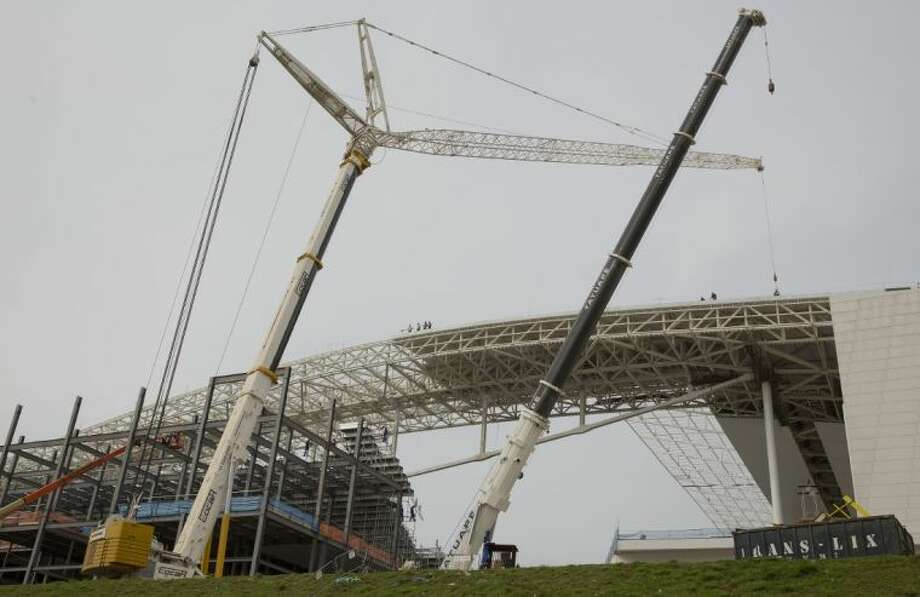 Construction cranes stand over the unfinished Itaquerao stadium on Tuesday in Sao Paulo, Brazil. Photo: Andre Penner