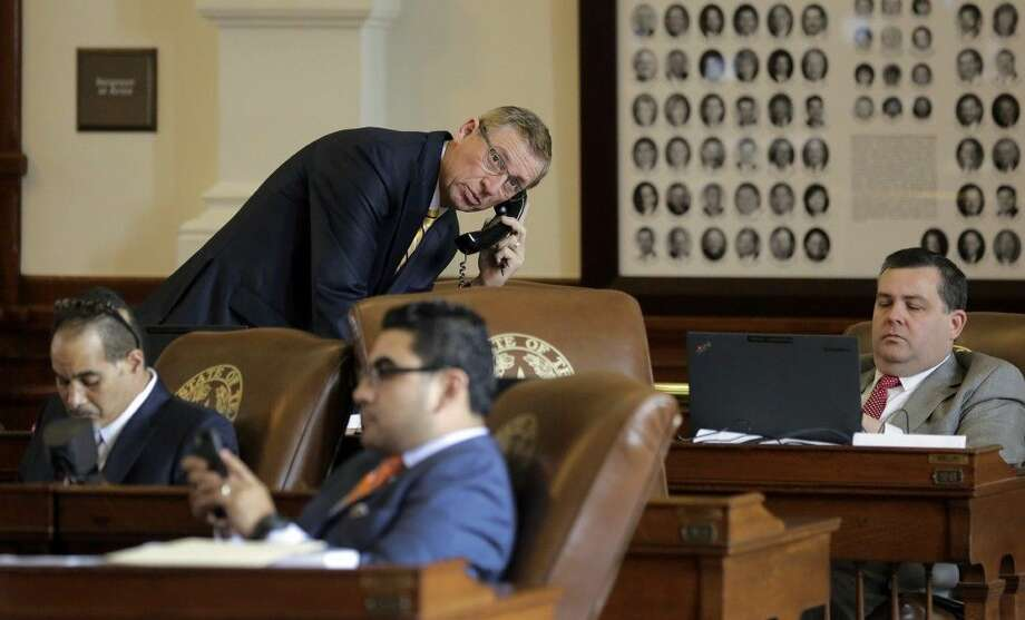 Texas Rep. Byron Cook, R-Corsicana, top left, talks on the phone in the House Chamber of the Texas Capitol in Austin. Photo: Eric Gay