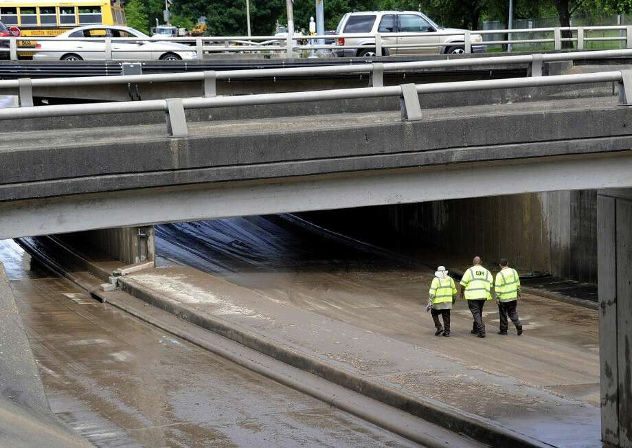 City of Houston workers walk along a wet, muddy, low stretch of Allen Parkway near downtown Houston, Wednesday. Photo: Pat Sullivan