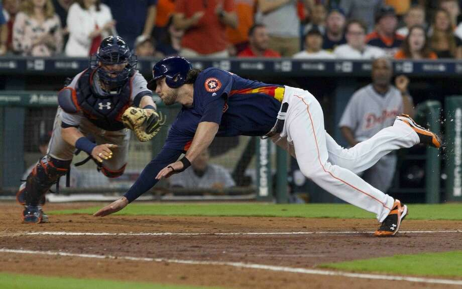 Jake Marisnick, of the Houston Astros, slides past the tag at home by catcher Jarrod Saltalamacchia, of the Detroit Tigers, to score off a two-run single by Jose Altuve during the fourth inning of an MLB baseball game Sunday, April 17, 2016. Photo: Jason Fochtman