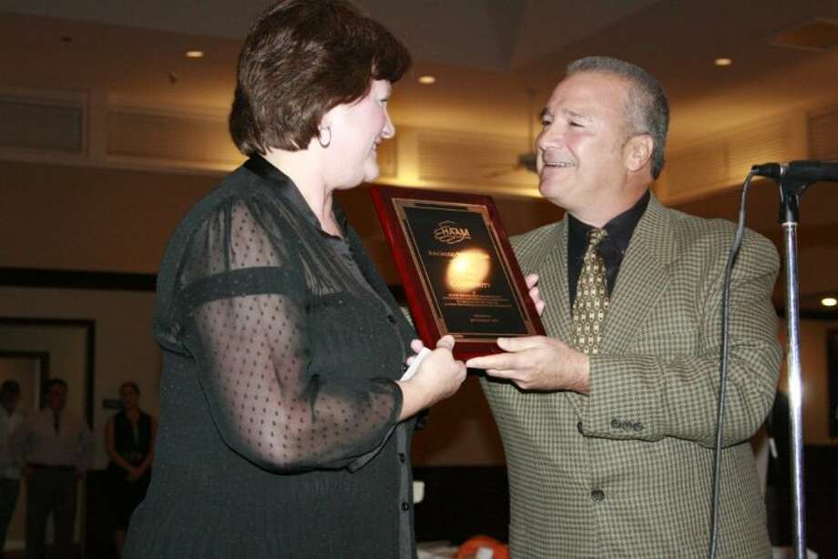 Tony Raffa, right, hands to recognition plaque to current Kingwood Women's Club president Debra Spears at the annual HAAM Pillars of the Community recognition dinner Sept. 19, 2013.