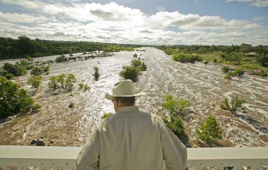 Tex Toler watches the Llano River rise, Friday in Llano, Texas, after another round of heavy rain. Photo: Jay Janner