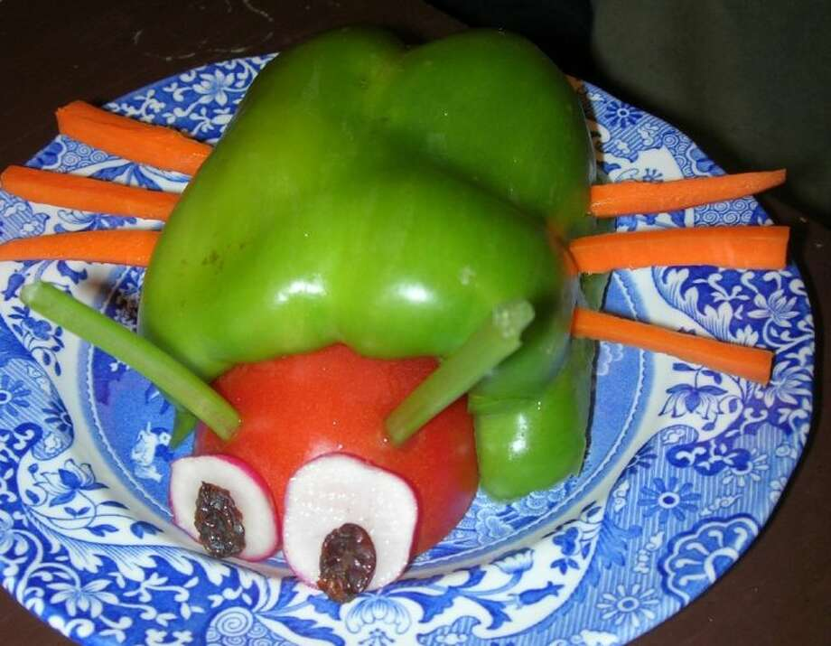 A green bug made from a bell pepper half, celery sticks, a tomato, carrot sticks, banana slices and raisins. It's a fun way to get kids to snack on fruits and vegetables.
