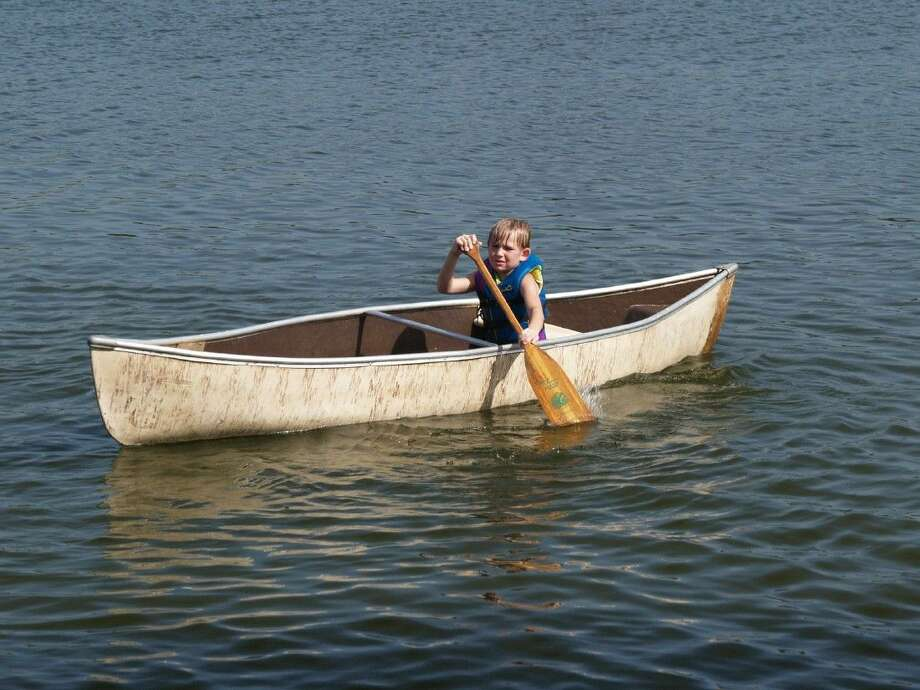 My grandson shows off his canoeing skills on the lake complete with life jacket and covered with sunscreen.