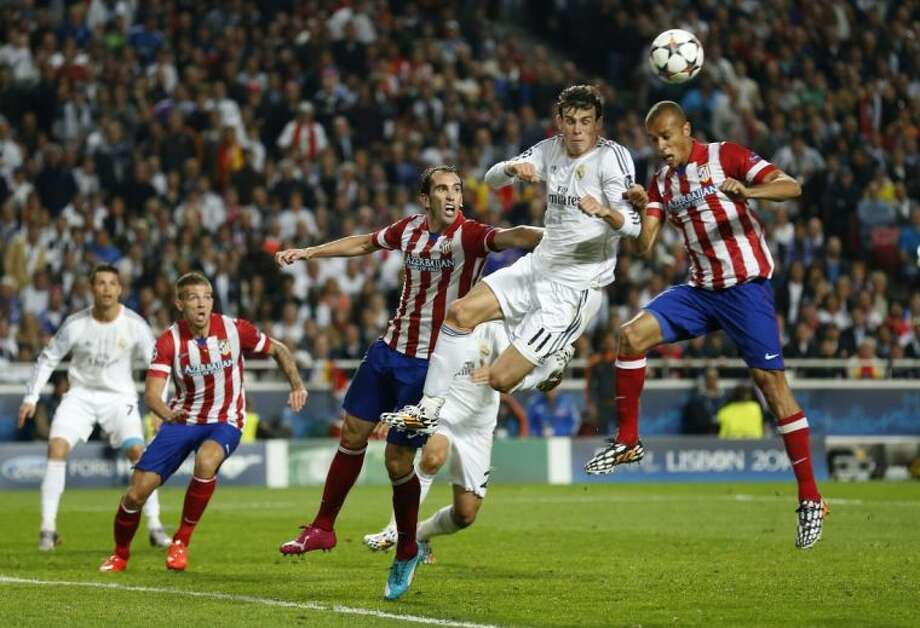 Real Madrid's Gareth Bale, second from right, jumps for the ball with Atletico's Miranda in the Champions League final in Portugal on Saturday. Real Madrid won 4-1. Photo: Andres Kudacki