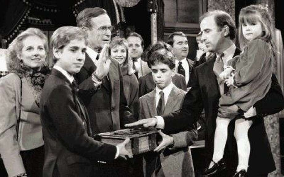 FILE - In this Jan. 3, 1985 file photo, Sen. Joe Biden (D-Del.) holds his daughter, Ashley, while taking a re-enacted oath of office from Vice President George Bush during a ceremony on Capitol Hill in Washington as his sons Beau, foreground, and Hunter hold the bible. Photo: Lana Harris