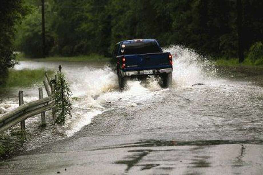 A truck drives through high water Monday on Magnolia Bend Drive. Photo: Michael Minasi