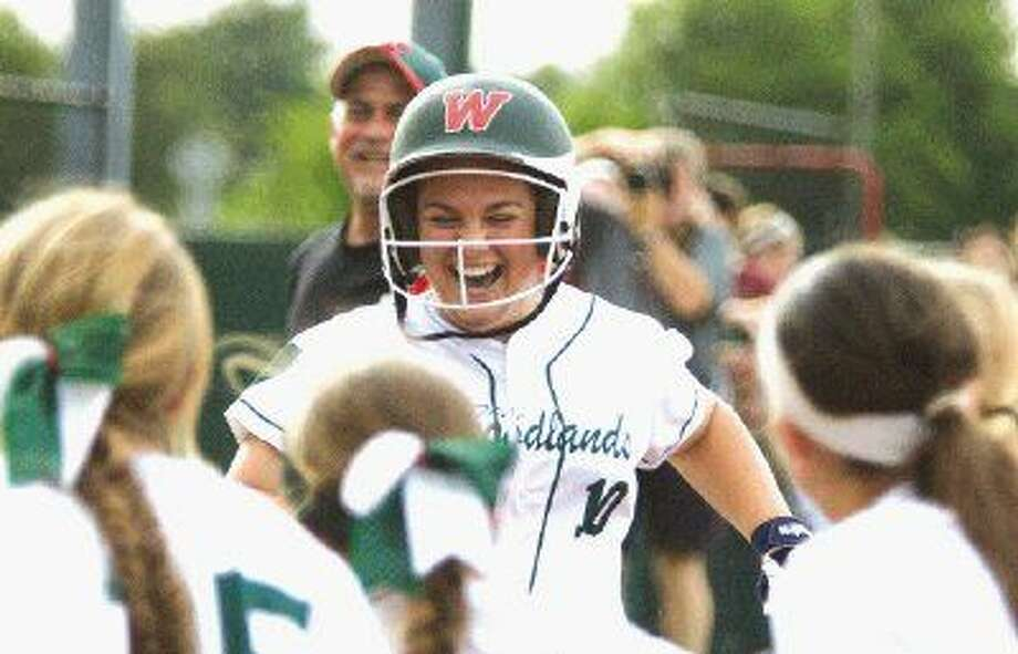 The Woodlands' Kelcy Leach comes in to score after hitting a walk-off home run in the bottom of the eight inning to give the Lady Highlanders a 5-4 win over Lake Travis in the Region II-6A regional finals in Mumford Saturday. To view or purchase this photo and others like it, visit HCNpics.com. Photo: Jason Fochtman