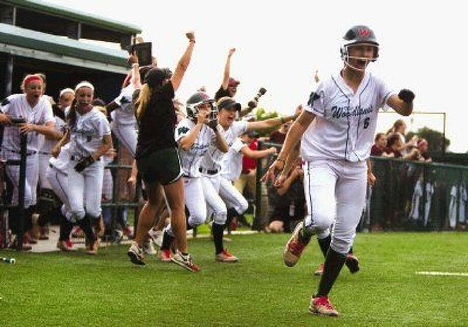The Woodlands players celebrate after Kelcy Leach's walk-off home run in the bottom of the eighth inning that sent the Lady Highlanders to the Class 6A state tournament. Photo: Jason Fochtman